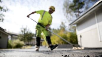 En yrkesarbetare jämnar ut asfalt med en asfaltsraka.