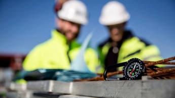 Bild på en kompass med två NCC-medarbetare som interagerar i bakgrunden.
