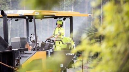 Bild på en medarbetare och maskin som arbetar med asfalt.