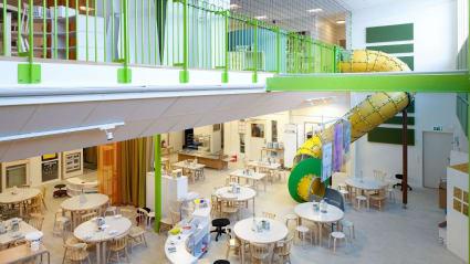 En matsal i en skola. Små bord strödda kring golvet, med stolar för både vuxna och små. En rutschkana glider ner från övre till undre våning.