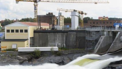 Bild på en vattenkraftstation, där vatten forsar i en flod samtidigt som lyftkranar, bostadshus och skog syns i bakgrunden.