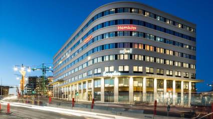 Huset Torsplan i Stockholm. Byggnaden och kringgärdande trafik lyser upp i kvällsmörkret.