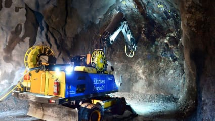 En borrmaskin hackar längs bergsväggen under bygget av en tunnel