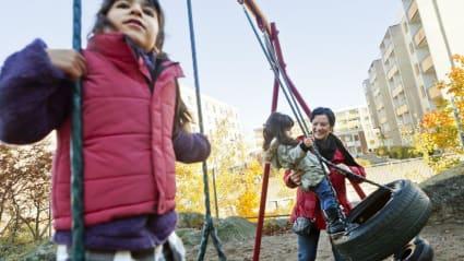 Närbild på när ett barn gungar och en vuxen hjälper ett annat barn med gungan. I bakgrunden ses lägenhetshus och en skola.