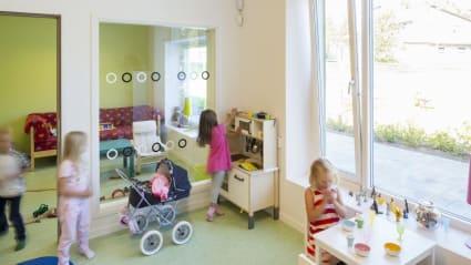 Bild på ett lekrum där flera barn genomför olika aktiviteter och nöjen.