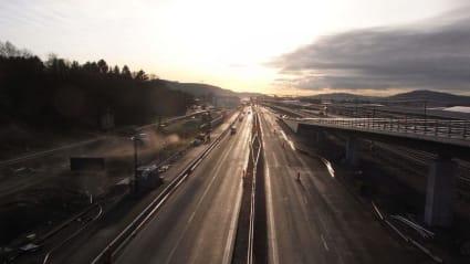 Två fordonsvägar - en järnväg och en asfaltsväg, båda under utbyggnad och på väg mot horisonten.