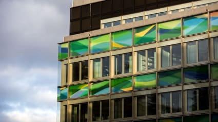 Närbild på en fasad som till största delen består av fönster, både färgade och ofärgade.