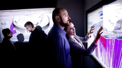 I ett mörktlagt rum inspekterar flera personer olika 3D-modeller som projiceras mot väggen.