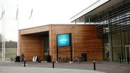 Bild på Skövde Arenas ingång, med träpaneler som blir en kontrast mot huvudbyggnadens glasfasad.