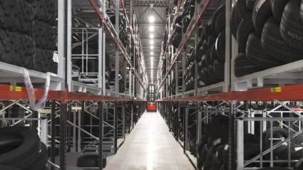 Blick mot en lång gång i en lagerlokal, med hyllor fyllda av däck på båda sidor. Längst fram i gången syns en röd truck.