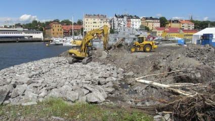 Grävmaskiner sanerar sjönära mark, med byggnader i bakgrunden.