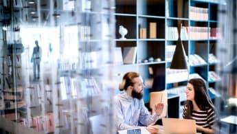 NCC har fem affärsområden. På bilden ser du två personer som diskuterar i en biblioteksliknande miljö.