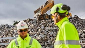 Bild på två byggarbetare i förgrunden, i bakgrunden syns en hjullastare tippa av ett lass med  stora stenar