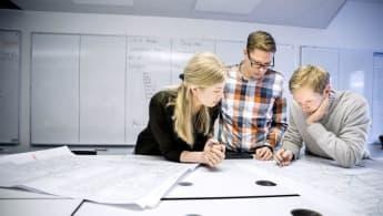 Tre personer studerar en skiss tillsammans. I bakgrunden syns en whiteboard med skrivelser.