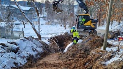 En grävmaskin gräver i marken för utbyggnad av VA-nät, i vinterskrud.