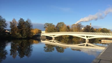 En cykelbro sträcker sig över floden, med träd och bebyggelse som reflekterar i vattnet.