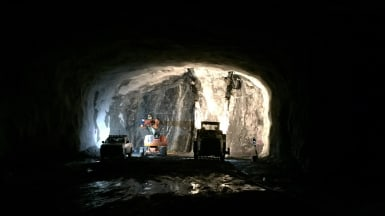 I en delvis upplyst bergtunnel arbetar byggmaskiner, med andra fordon närvarande.