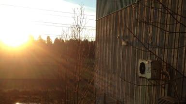 Solgryningen lyser upp Antuna pumpstation och en bil intill, samt naturen i bakgrunden.