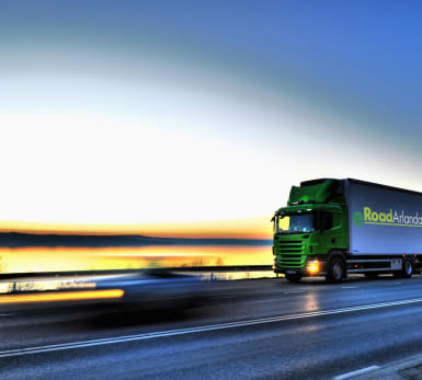 A truck zooms past the road with the dawning horizon and sea in the background.
