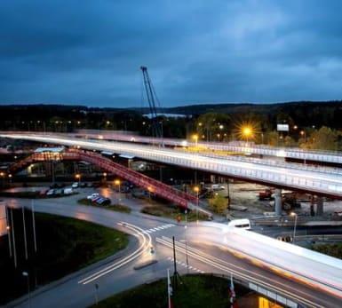 NCC bygger bron vid Rotebro. Flygbild över viadukten i Rotebro, lång exponeringstid gör att endast bilens strålkastare syns.