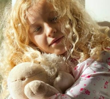 A child leans against a window while holding a bear.