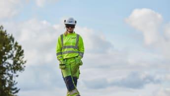 Bild framifrån på en yrkesarbetare med halvmolnig himmel i bakgrunden.