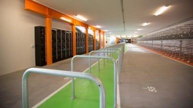 På bilden syns ett långt cykelgarage med många angöringsplatser och förvaringsskåp till vänster.