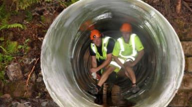 Två yrkesarbetare poserar i en nyanlagd vägtrumma.