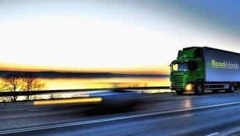 En lastbil kör längs med en väg med solen på nedgång i horisonten. På lastbilen läses