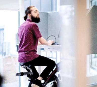 En person tränar på en spinningcykel samtidigt som han arbetar vid ett särskilt skrivbord.