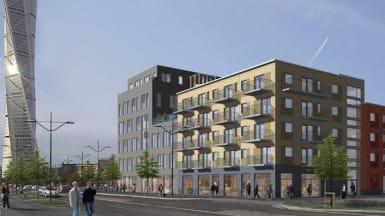 De nya bostäderna vid kvarteret Klyvaren, med gula och grå fasader. Den gula byggnaden har balkonger mot gatan, medan den gråa har ojämnt takhöjd.
