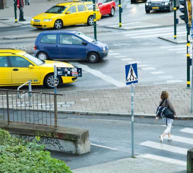 Bild på en aktiv vägkorsning med övergångsställen, trafiksignaler, trafik och fotgängare.