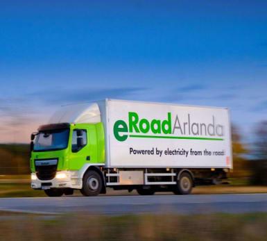 Bild på en lastbil märkt eRoadArlanda, som kör utmed en landsväg.