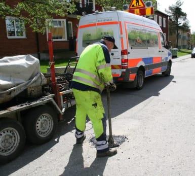 En arbetare lagar ett potthål vid en lugn flerbostadsväg.
