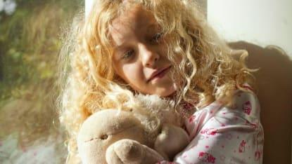 En ung flicka håller i sin nalle, medan hon lutar sig mot ett fönster där solen skiner igenom.