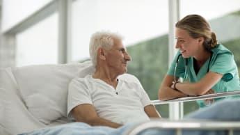 En äldre sjukhuspatient ligger i en säng och interagerar med en sjuksköterska.