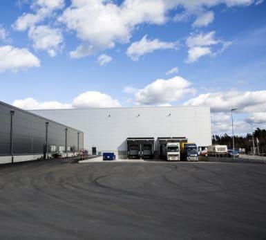 Vy över en logistikhall med ny asfaltering, med parkerade lastbilar som står redo för transport.