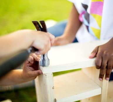 Närbild på två par barnhänder som snickrar med hammare i en liten konstruktion.