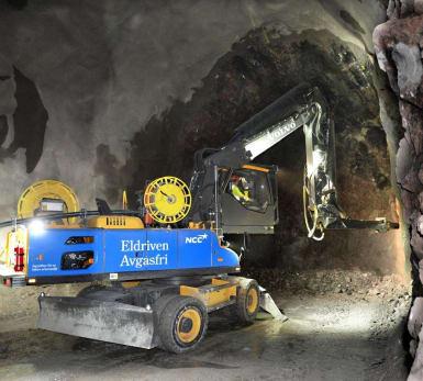 En maskin knackar bergväggen vid utbyggnad av en spårtunnel.
