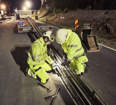 Två arbetare förbereder elskenan för en elektrisk väg.
