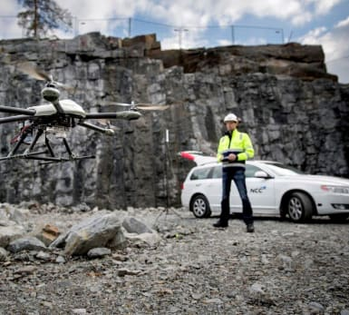 A workers steers a drone from the rocky ground, with his car in the background.