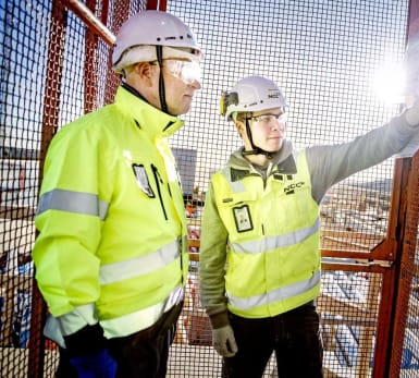 Två personer inspekterar en byggarbetsplatshiss. Den ena trycker på hissknappen.