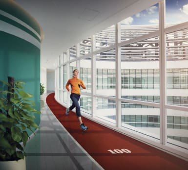A person runs in an indoor running track, inside an office building.