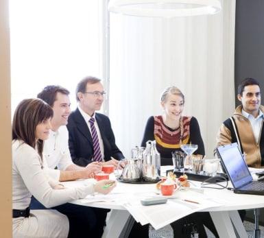 Fem personer sitter kring ett bord och tittar på någonting utanför bild.