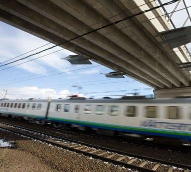 Montagebron bildar en viadukt över tågspår, med ett tåg susandes under.