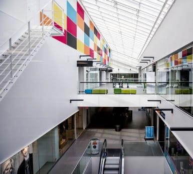 Golv, väggar och öppningar bildar en tydligt kvadratisk design i detta köpcentrum, med både vita och färgglada inslag.