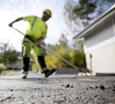 A worker flattening the pavement with the help of a special tool.