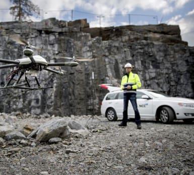 Bild på en multikopter i förgrunden, och en medarbetare som styr den i bakgrunden.