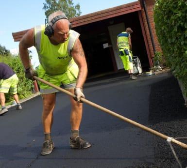 Tre arbetare jämnar ut och underhåller asfalt vid en garageuppfart.