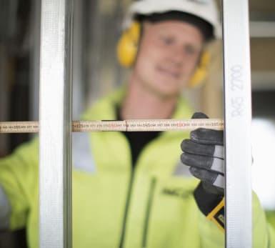 En arbetare mäter avstånd mellan två stänger med hjälp av en linjal.
